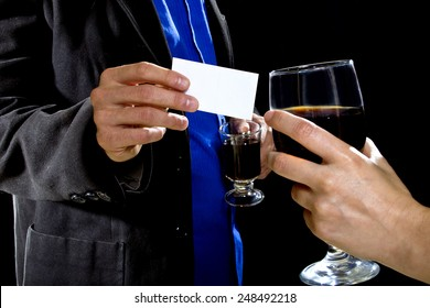 businessman handing over business card to a female at a bar