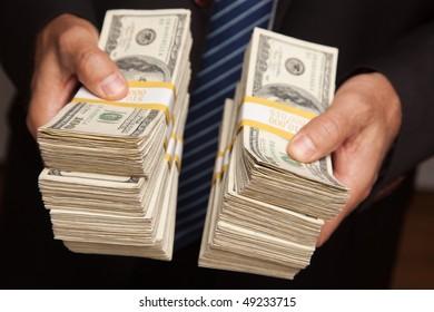 Businessman Handing Over Stacks of Hundred Dollar Bills.