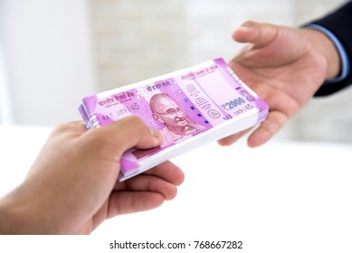 Businessman handing over wad of crisp new Indian rupee banknote money to his partner against white blur background