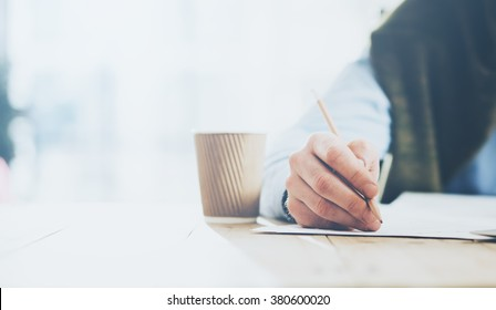 Businessman handing pencil hand and writing message. Blurred background, horizontal closeup.