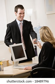 Businessman handing receptionist his business card