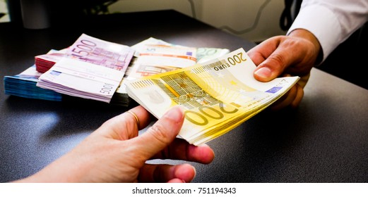 A businessman handing a stack of two hundred (200) Euro notes to a female hand over a desk