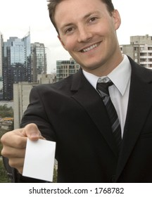 A businessman is handing you a blank business card.