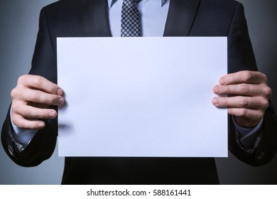 businessman hands closeup. a man in a suit holding a blank form. blank for placement of graphics, slogans, text.