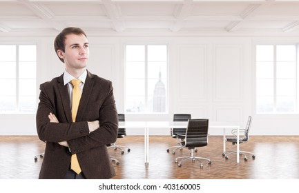 Businessman with hands crossed, meeting table in big hall, windows, New York view, luxury parquet. Concept of new office.