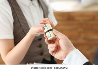 Businessman hands a cutlet out of money to a woman in the form of a bribe of salary in an envelope a dollar equivalent from hand to hand