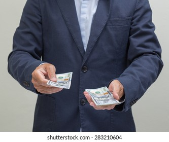 Businessman with hands giving dollar banknote, US dollars