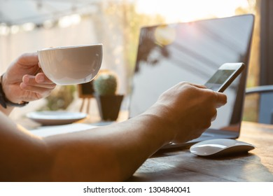 Businessman hands holding coffee cup and cell phone with laptop on table.