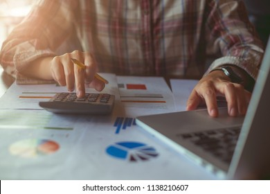 Businessman hands holding pen working on calculator and financial paperwork. Account and Saving concept.