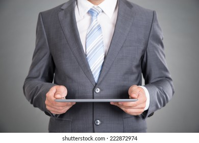 Businessman hands holding tablet computer. Over gray background