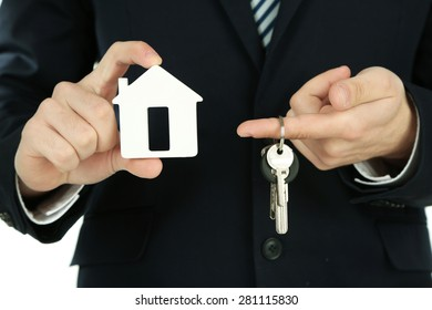 Businessman hands with keys and model of house, closeup