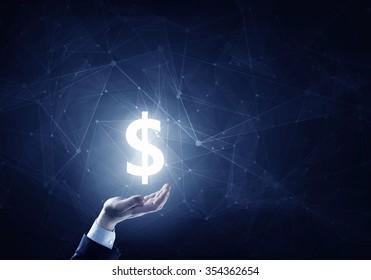 Businessman hands on dark background holding glowing dollar sign