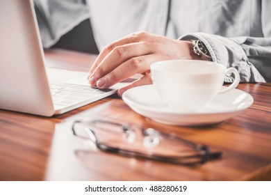 Businessman Hands on a Rustic Wooden Table with laptop Computer a Cup of Coffee. good photo