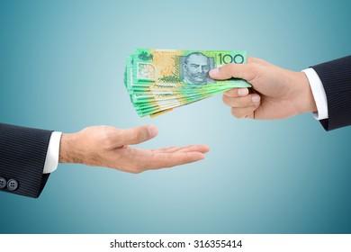 Businessman hands passing money, Australian dollar (AUD) banknotes, on gray background