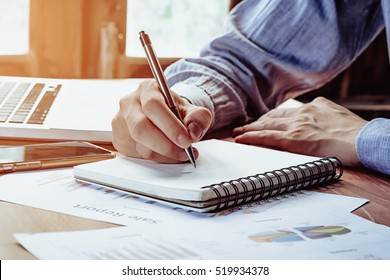 Businessman hands with pen writing notebook  on office desk table close up. Business concept.