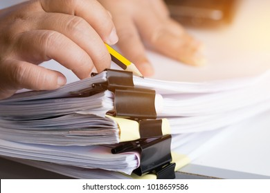Businessman hands searching unfinished documents stacks of paper files on office desk for report papers, piles of papers sheet achieves with clips on desks, Document is written, drawn,presented.
