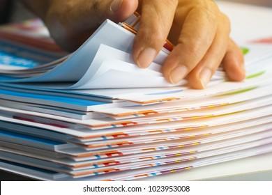 Geschäftsleute, die unfertige Dokumente durchsuchen, legen Papierstapel auf dem Büroschreibtisch für Berichtspapiere auf, stapeln von Blatt erreichen mit Clips auf dem Tisch, Dokument wird geschrieben, gezeichnet, präsentiert.