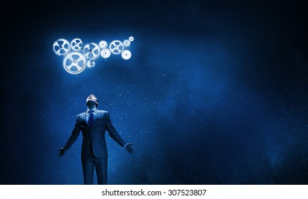 Businessman with hands spread apart looking above at gears mechanism