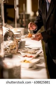 Businessman hands taking food in buffet line indoor in luxury hotel