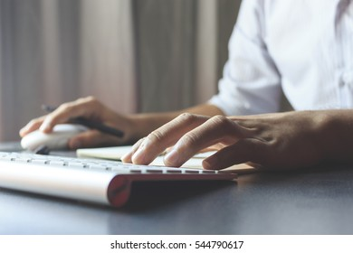 businessman hands typing computer pc concept with film colors tone, soft-focus in the background. over light