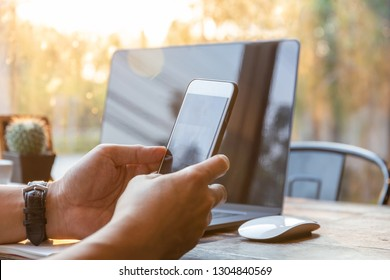 Businessman hands using cell phone with laptop on table in sunlight.