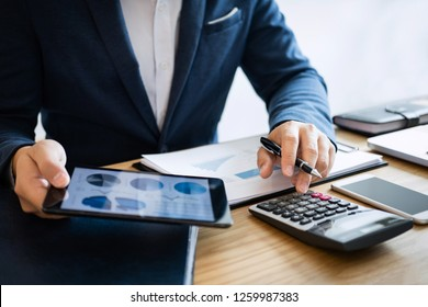 Businessman hands using text information on digital tablet to analyze financial statistical chart data and calculate cost of investment project.