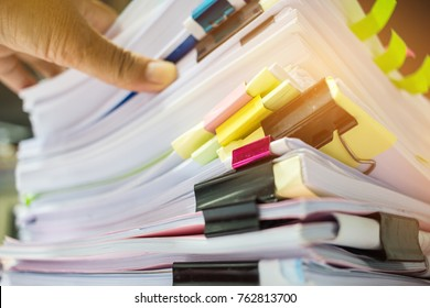 Businessman hands working in Stacks of paper files for searching information on work desk office, business report papers,piles of unfinished documents achieves with clips indoor,Business busy concept