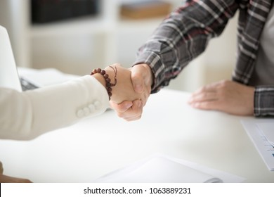 Businessman handshaking businesswoman making deal or showing respect, female and male hands shaking as concept of good teamwork and collaboration, gratitude for help or advice, close up view