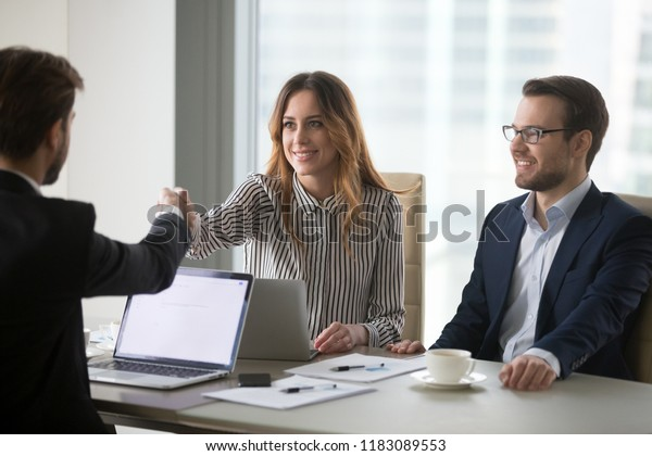 Businessman handshaking female business partner meeting in office ready for negotiations, diverse millennial colleagues shaking hand thanking for successful conference or talk. Partnership concept