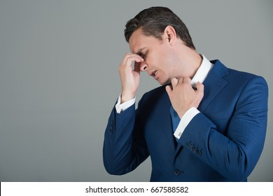 businessman, handsome man or boss with headache and stylish hair, haircut in fashionable blue formal suit, white shirt and tie on grey background.