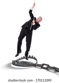 Businessman hanging onto a rope, fearing trap below, isolated on white