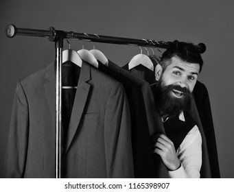 Businessman with happy face near jackets on blue background. Consumerism and elegance concept. Shop assistant or seller hides among suits on clothes hangers. Man with beard in vest by clothes rack.