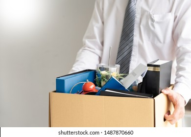businessman has a brown cardboard box and resignation letter write reason for resigning from work or unemployment and change job concept