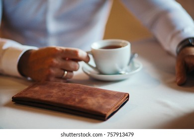 The businessman has coffee in cafe. Nearby the purse lies