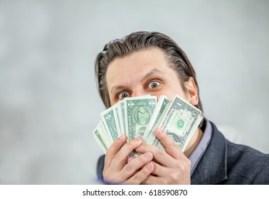 A businessman has lots of money in his hands and he is showing a weird face.