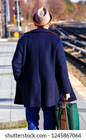businessman with hat and blue coat walking at train station