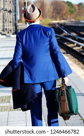 businessman with hat and blue suit walking at train station