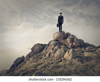businessman with hat and briefcase on the top of mountain