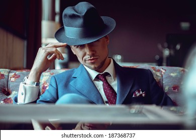businessman in a hat in a restaurant