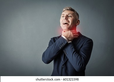 Businessman having asthma attack or choking can't breath on gray wall background