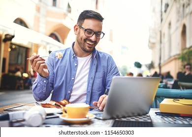 Businessman having breakfast and doing his work in cafe.