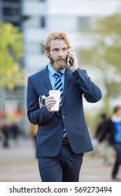 Businessman having a coffee break outside and talking on the phone