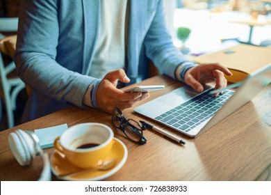 Businessman having coffee and doing his work in cafe. Close up concept.