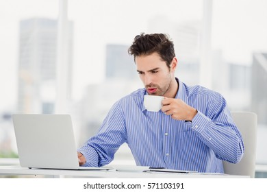 Businessman having a cup of coffee and working on laptop in office