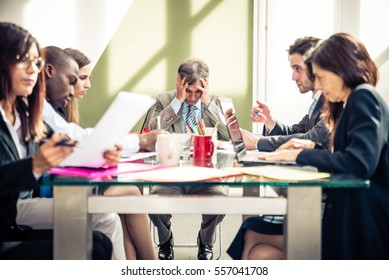 Businessman having headache during a business meeting - Depressed person with financial troubles