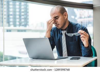 Businessman having headache and working on laptop in office with city building background. Health concept, Office syndrome.