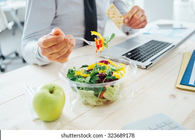 Businessman having a lunch break at desk, he is eating fresh salad and holding a cracker, unrecognizable person