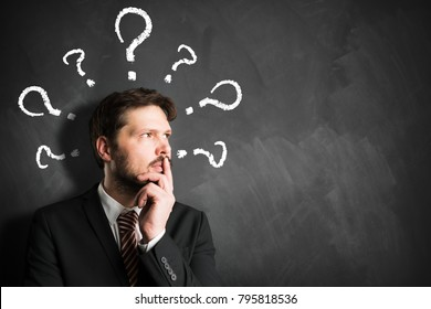 businessman having many questions symbolized as questionmarks on a blackboard over his head