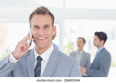 Businessman having phone call while his colleagues discussing in the office