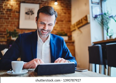 Businessman having phonecall through wireless headphones while working on tablet in cafe